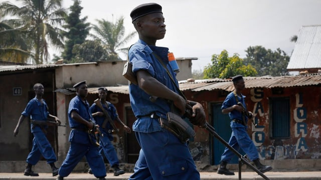 Fünf blau gekleidete burundische Polizisten mit Gewehren patrouillieren durch eine Strasse.