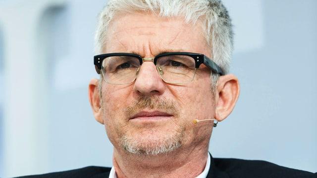 Ein Mann mit markanter Brille: Der obere Rand schwarz, unten nur das Glas.