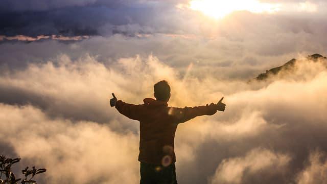Ein Wanderer steht auf einem Berg vor einem Nebelmeer und hält zwei Daumen hoch.