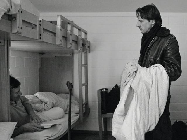 Mann mit Bettlaken in der Hand spricht mit Mann im Stockbett.