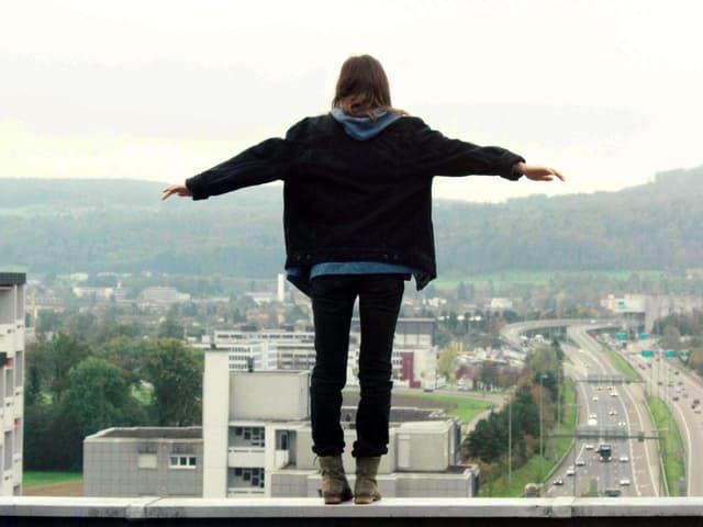 Ein Mädchen steht auf einem Rand eines Gebäudes.
