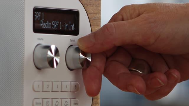 Eine Hand dreht an einem Einstellknopf eines DAB-Radios.