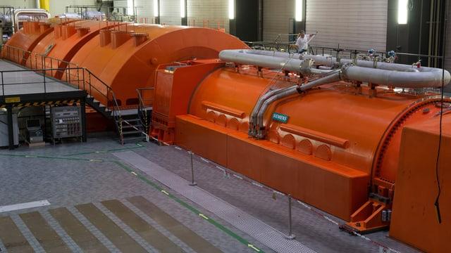 Eine grosse, orange, halbrunde Abdeckung ist zu sehen, darunter verborgen ist der Generator.