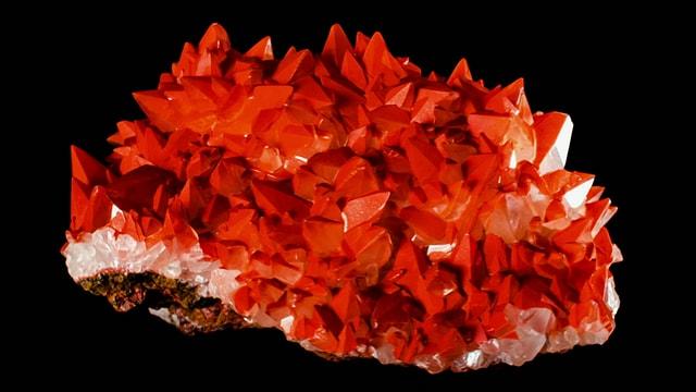 Ein roter Kristall auf schwarzem Hintergrund.
