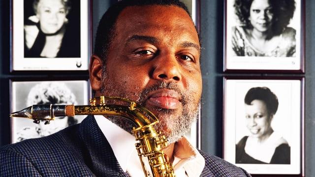 Der Saxophonist Arthur Blythe vor Fotowand mit Jazzsängerinnen.