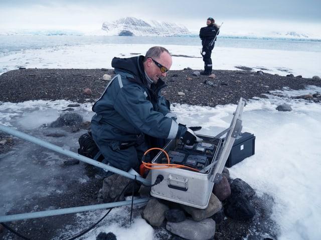 Ein Forscher packt Schneeproben in eine Kiste.