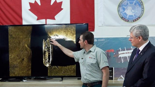 Kanadas Premierminister Stephen Harper rechts hört zu, wie ein Ranger von Parks Canada das Sonarbild mit dem Wrack der Franklin-Expedition erklärt.