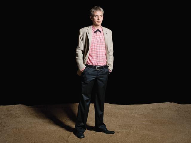 Reto Scherrer trägt das Schwingeroutfit «Der Edle» mit schwarzen Hosen, rotweissem Hemd und beigem Veston.