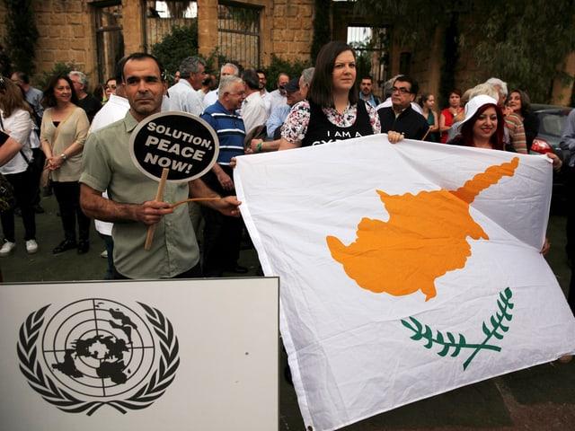 Ein Mann und eine Frau demonstrieren mit einer zypriotischen Flagge für die Vereinigung.