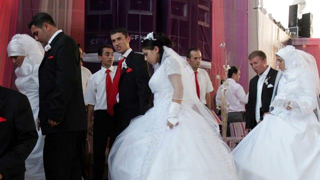 Ehepaare (Frauen in weissem Kleid, teilweise mit Schleier, Männer im Anzug) verlassen händchenhaltend eine Bühne