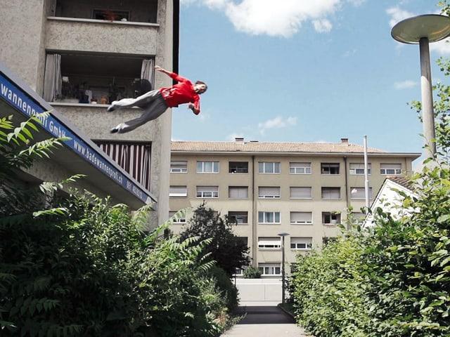 Mann springt von einem Dach.