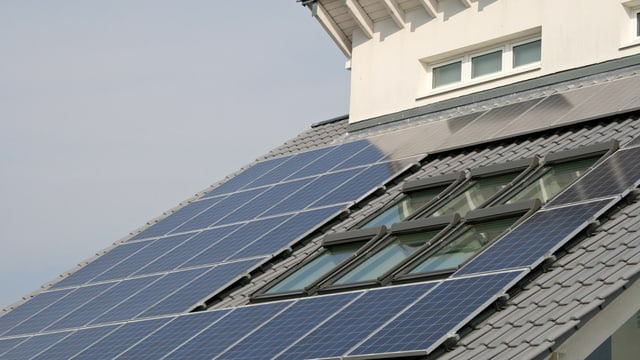 Panels für Solarstrom auf einem Hausdach umrahmen Dachflächenfenster.