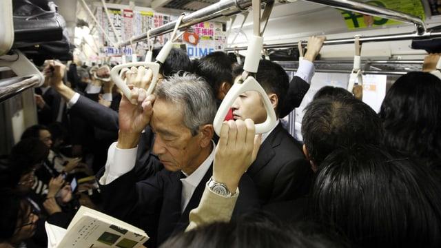 Japaner stehen dicht gedrängt in einem Zug.