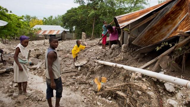 Menschen vor einem zerstörten Haus.