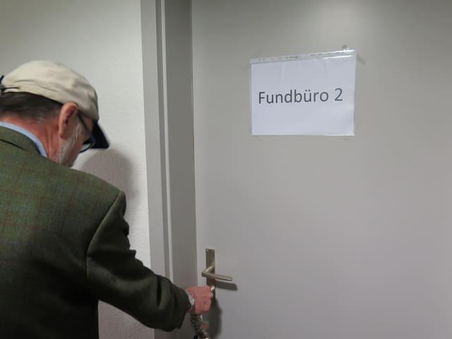 Mann mit Kappe schliesst Tür ab.