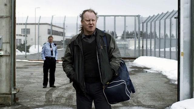 Ein Mann steht mit dem Rücken zum Tor eines Gefängnisses. Im Hintergrund steht ein anderer Mann in einer Uniform.