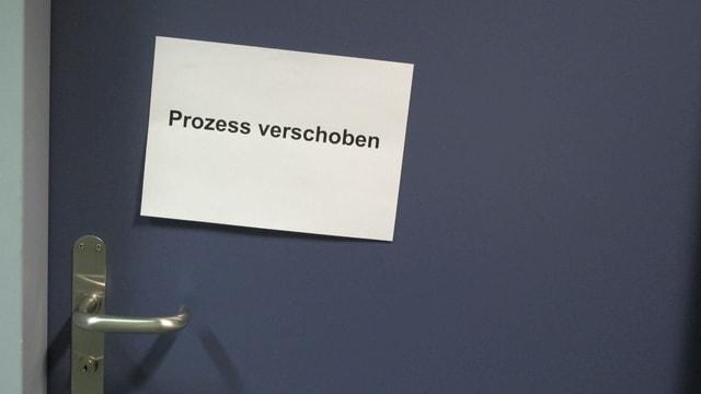 Schild «Prozess verschoben» an Türe.