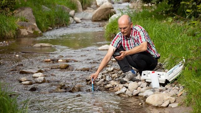Ein Mann entnimmt eine Wasserprobe aus einem Bach.