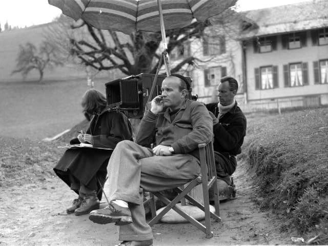 Franz Schnyder sitzt neben der Kamera unter einem Sonnenschrim und betrachtet die Szene. Skript und Kameramann sitzen daneben.