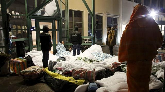 Fugitivs dorman giuadora avant l'uffizi d'immigraziun a Malmö.