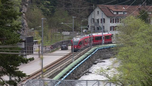 Ein Zug der RhB fährt neben der Strasse, die auf dem schmalen Talboden nach Meiersboden führt.