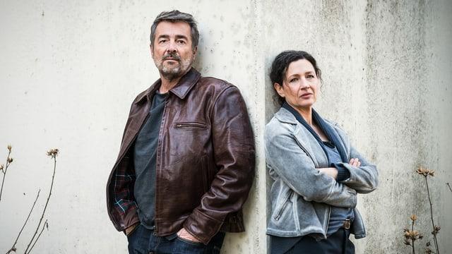 Mann mit Händen in den Hosentaschen und Frau mit verschränkten Armen lehnen an einer MAuer und schauen ernst in die Kamera.