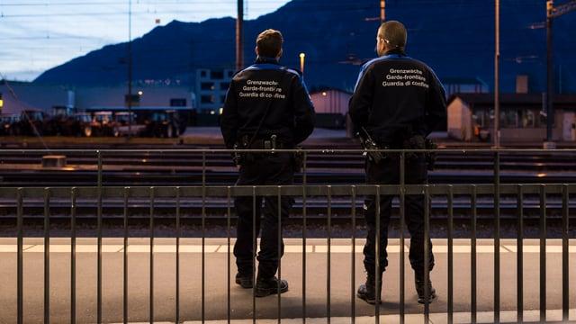 Zwei Mitglieder der Grenzwache stehen am Bahnhof