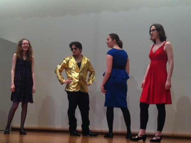 Männer und Frauen auf Bühne mit Kostümen