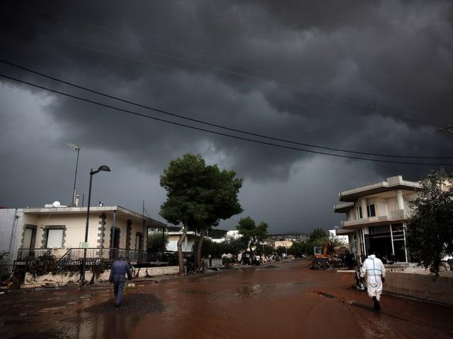 Am Himmel liegen schwarze Wolken. Die Strasse darunter ist überflutet.