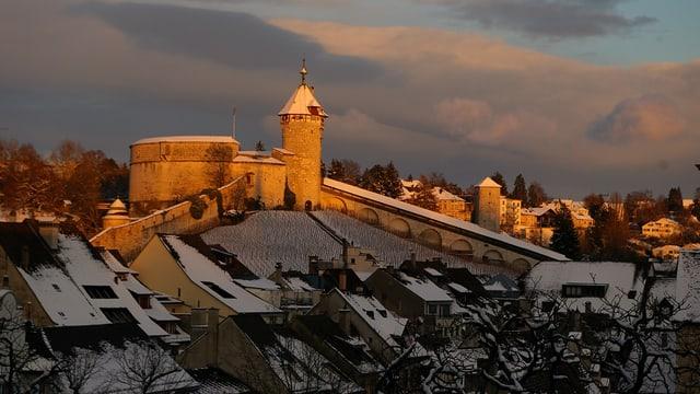 Blick über Altstadtdächer auf Schaffhasuer Munot-Burg im Schnee und Abendlicht