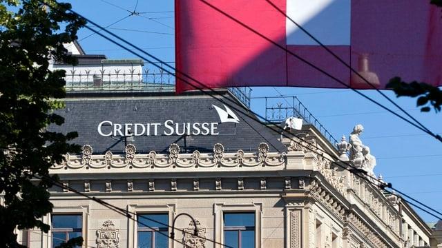 Schriftzug der Crédit Suisse auf dem Dach der Grossbank, davor der Ausschnitt einer Schweizerfahne