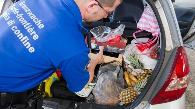 Ein Grenzwächter kontrolliert einen Kofferraum voller Waren.