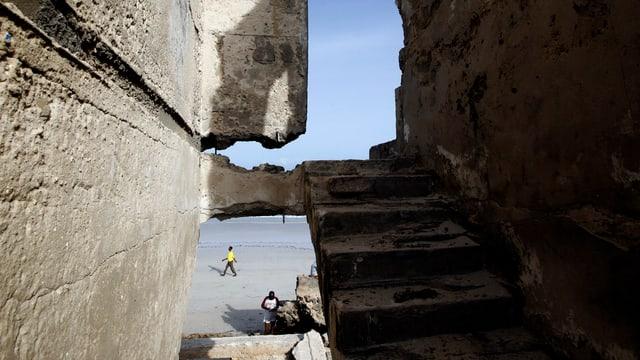 Durch die Trümmer einer Ruine sieht man auf einen Strand.