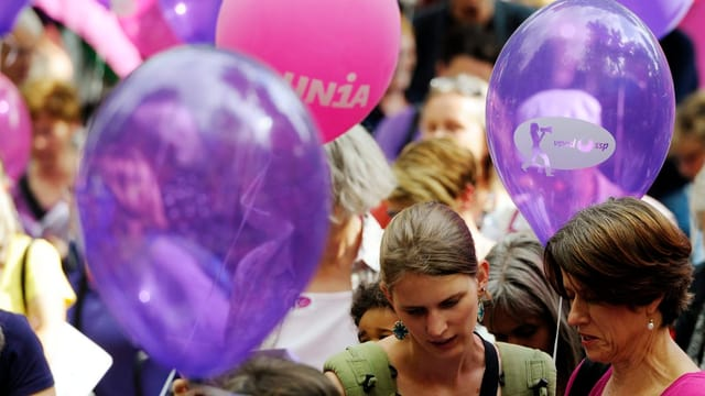 Frauen an einer Demonstration mit violetten und pinken Ballons.