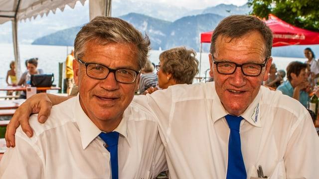 Zwei Männer in weissem Hemd mit blauer Kravatte.