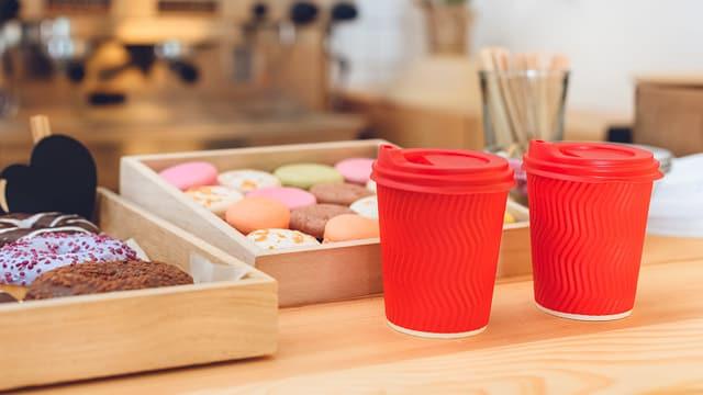 Zwei rote Plastikbecher auf einer Theke.