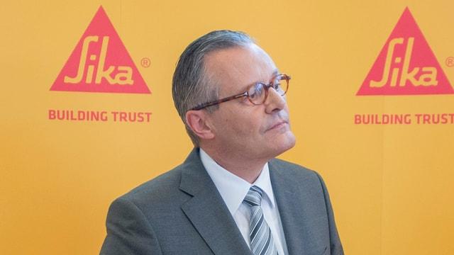 Sika-Präsident Paul Hälg an der diesjährigen GV vor einer gelben Wand mit zwei roten SIka-Logos