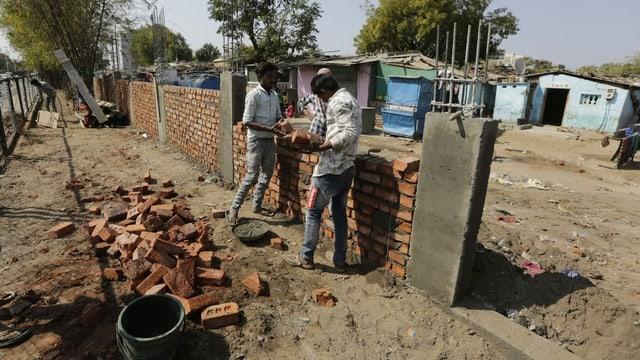 Zwei Arbeiter bauen eine Mauer aus Ziegelsteinen. Im Hintergrund ein Slum.