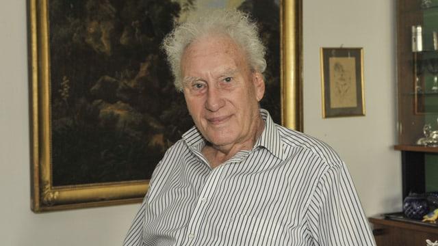 Portrait von Carl Miville, er schaut in die Kamera. Im Hintergrund sieht man einen Ausschnitt eines gemalten, dunklen Bildes im goldigen Rahmen und am Bildrand einen Teil einer Vitrine mit Pokalen.