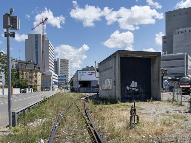 """Areal mit Bahngeleisen, undefinierbaren alten Gebäuden und dem Turm der """"Brenntag"""","""