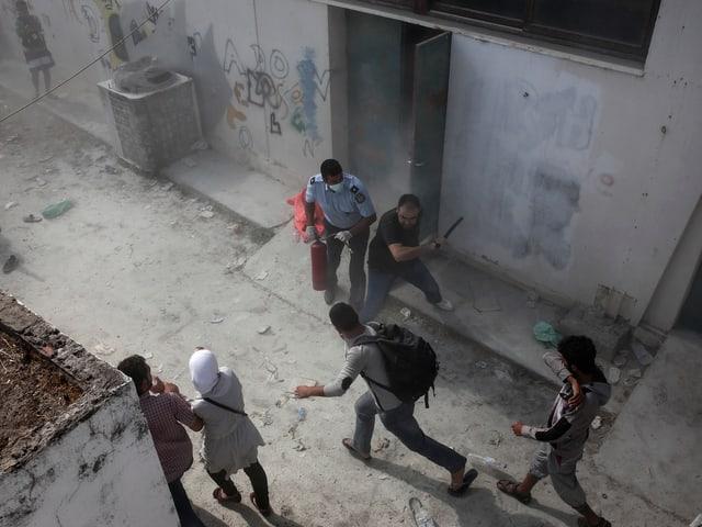 Ein Man greift mit einem Schlagstock einen Flüchtling an.