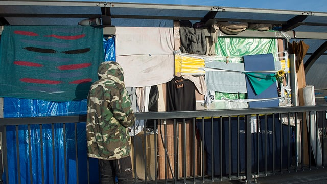 Obdachloser, der mit Tüchern und alten Sofas  in einem Velounterstand beim Bahnhof Sankt Johann seine Unterkunft eingerichtet hatte.