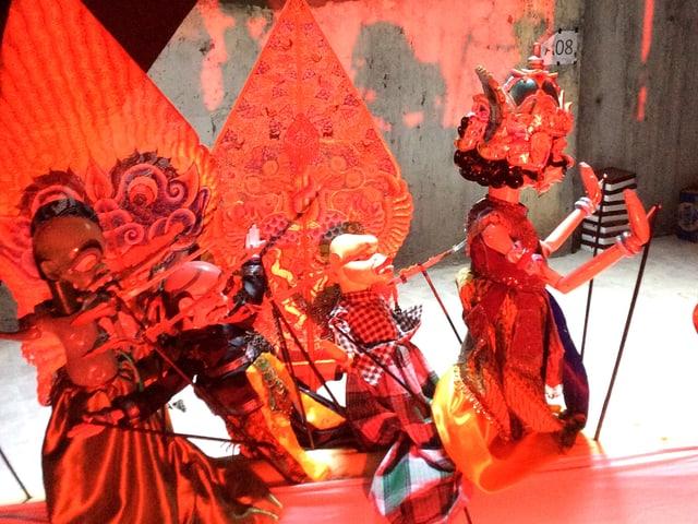 Puppen in roten Kostümen auf einer Bühne.