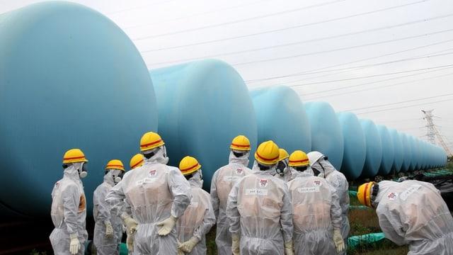 Arbeiter in Schutzanzügen stehen vor grossen, blauen, runden Containern