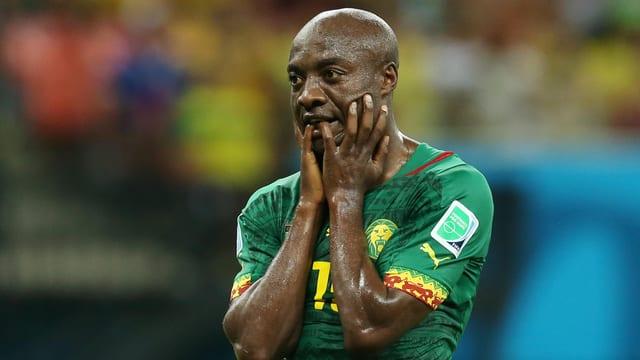 Kameruns Pierre Webo hält sich die Hände vors Gesicht.