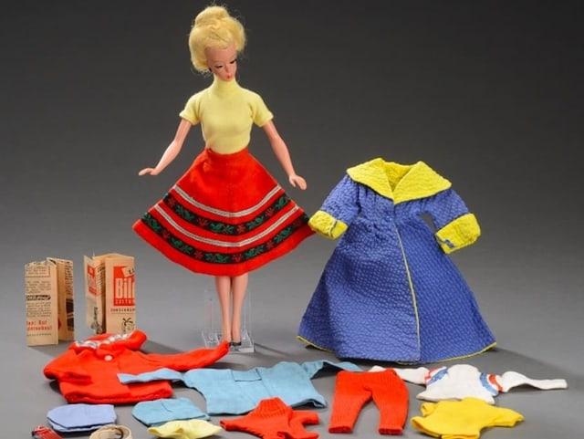 Eine Puppe und Puppenkleider.