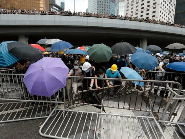 Demonstranten mit Regenschirmen bauen Barrikaden