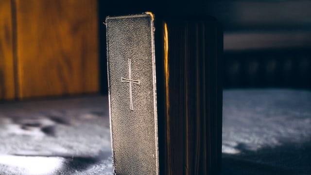 Ein Buch mit einem Kreuz steht auf einem Tuch.