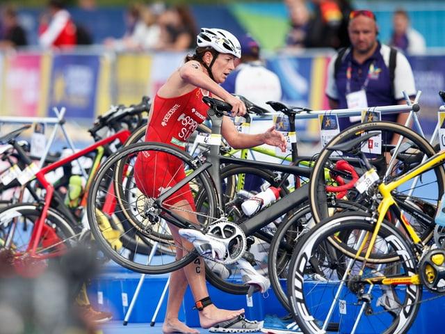 Nicola Spirig greift in der Wechselzone nach ihrem Rad.