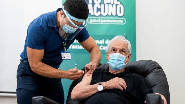 Präsident Sebastián Piñera erhält die Impfung von einer Pflegeperson.